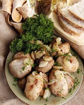 Шляпки грибов на гриле с чесноком и зеленью