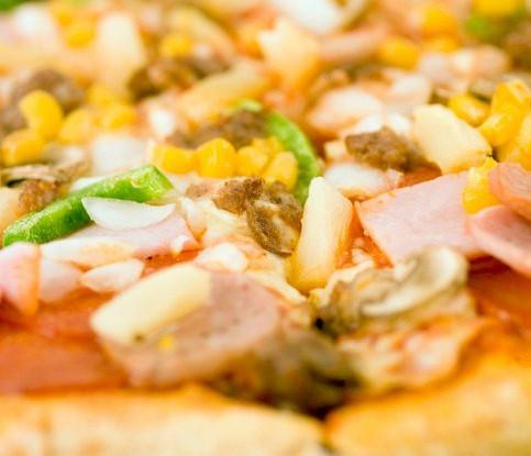 Пицца с ананасами, колбасой, сладкой кукурузой и томатами