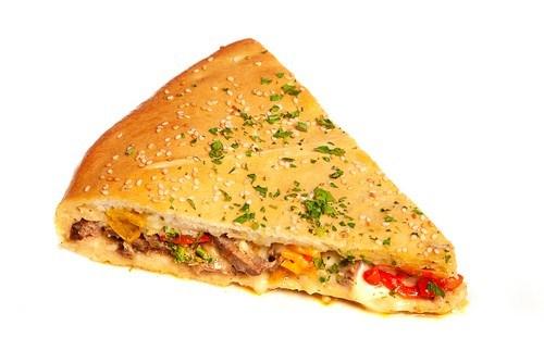Закрытая пицца с сельдью, томатами и базиликом