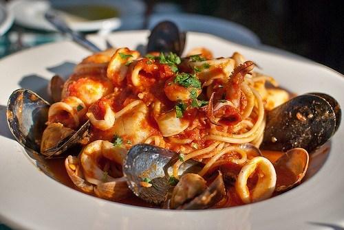 Паста с морепродуктами, зеленью и чесноком в томатном соусе